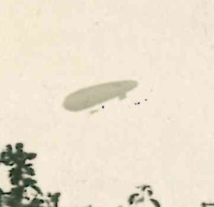 Cropped detail of a private back garden photograph of an airship or possible Zeppelin, location and date unknown. (Image source: copyright World War Zoo Gardens collection)